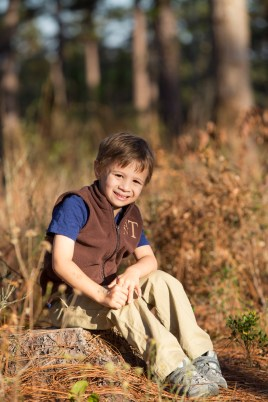 A young boy sits on a stump in the Longleaf Pine Forest of Mobile, Alabama.