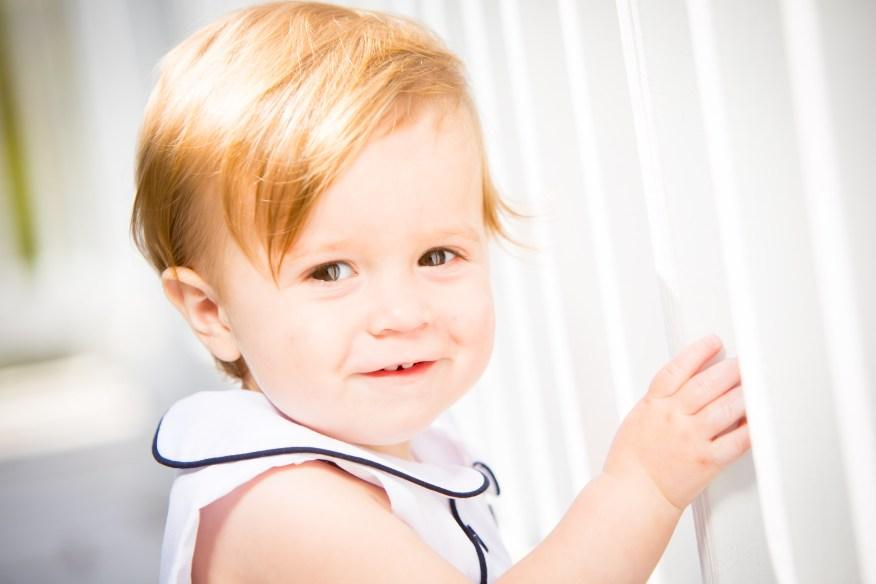 The sun highlights the one-year-old's auburn hair