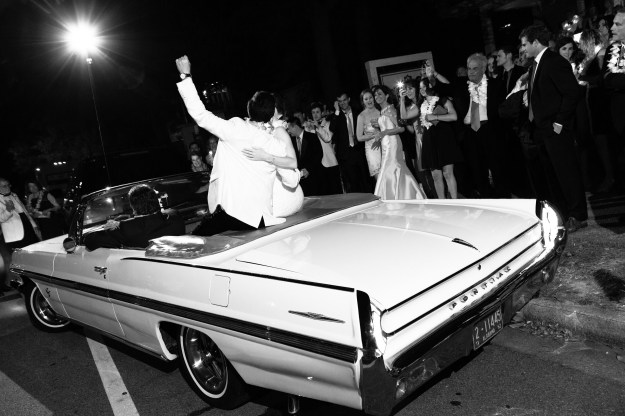 Bride and groom make their exit in an antique Pontiac