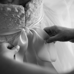Mom ties the bow on the bride's wedding dress as she gets ready at The Pillars of Mobile, Alabama