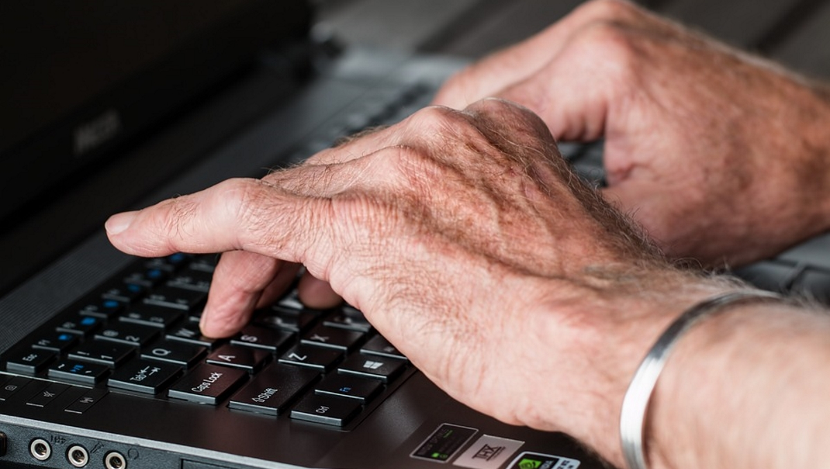 Old hands typing laptop