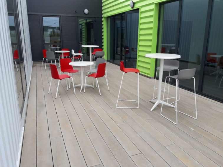 2ème espace réfectoire extérieur avec une alternance de tables hautes et basses Outdoor et de sièges Gelati en coloris blancs, gris et rouges