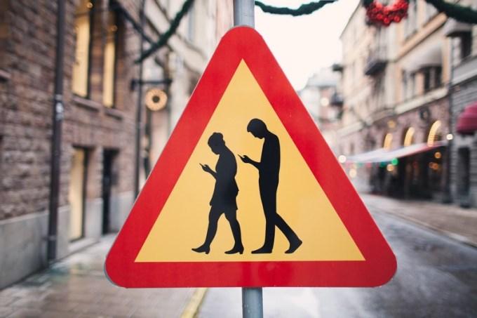 Znak drogowy ostrzegający przez smombie na ulicy