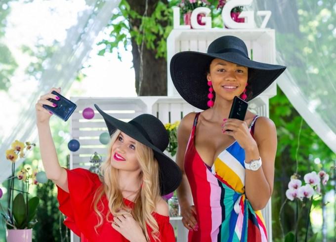 LG G7 ThinQ i panie w kapeluszach robiące sobie selfie