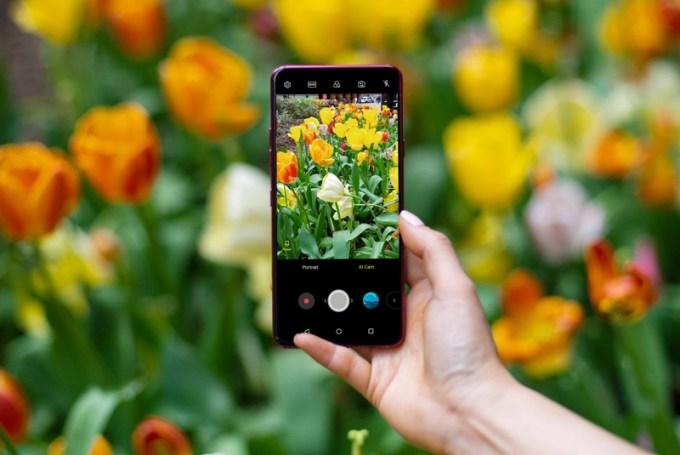 LG G7 ThinQ na tle pomarańczowych i żółtych tulipanów