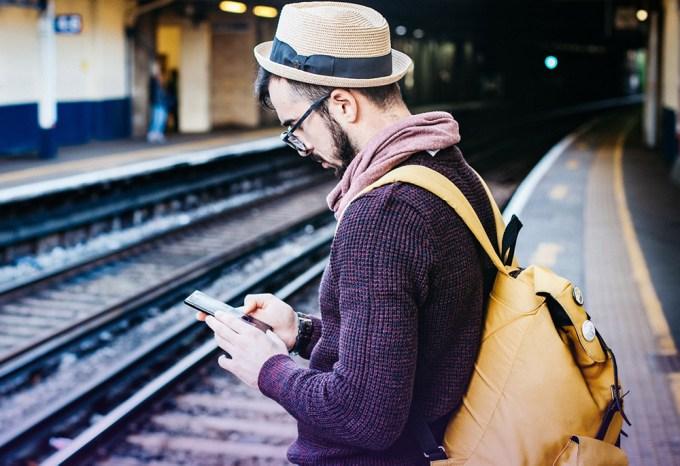 Bilety na pociągi przez smartfona - mężczyzna w kapeluszu ze smartfonem w dłoni na peronie kolejowym
