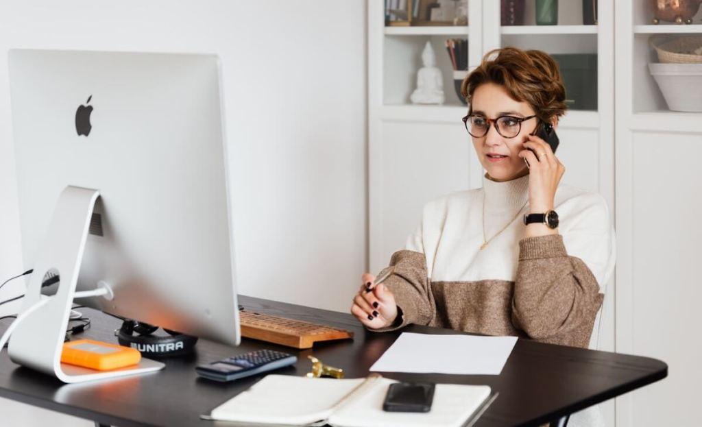 Kobieta siedząca przed komputerem i rozmawiająca przez telefon