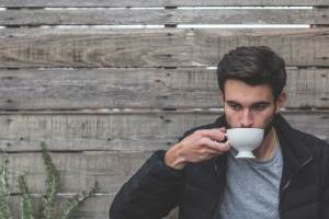 Man sipping cup of coffee outdoors