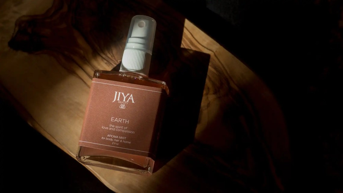 Bottle of Jiya Earth Aroma Mist on olive board with black background.