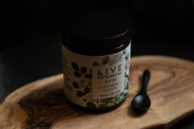 Jar of Live Botanical body scrub on wooden board with black background
