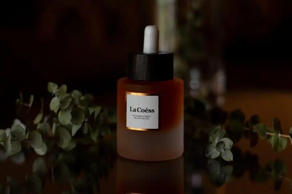 Women-owned beauty brand La Coess Facial oil bottle on dark background with eucalyptus leaves