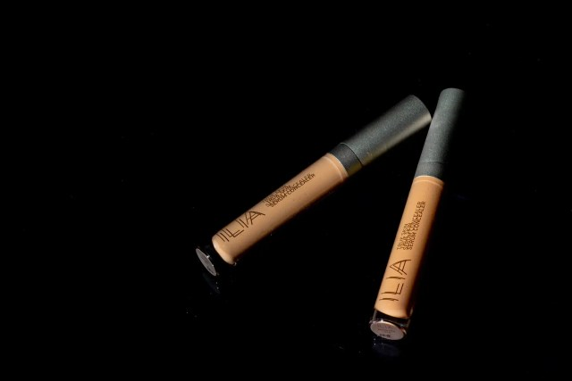 Ilia Concealer tubes on black background