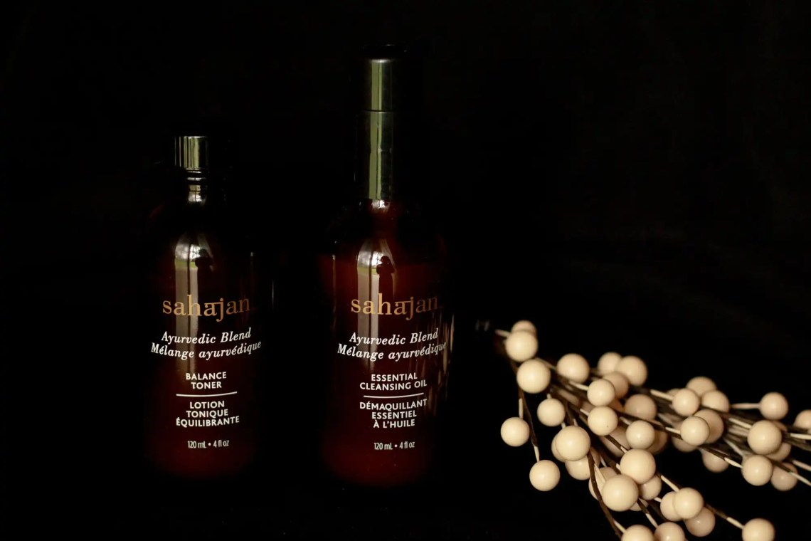 Sahajan Skincare brown bottles on black background with adjacent white flower buds