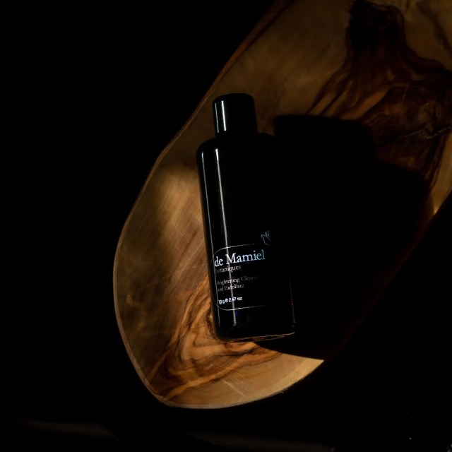 Bottle of De Mamiel Brightening Cleanse and Exfoliate on wooden board on black background