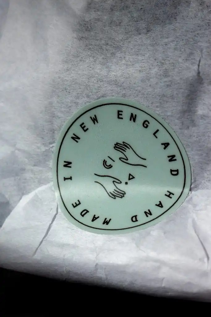 "Wild Lather packaging green sticker on white tissue reading ""Hand Made In New England"""