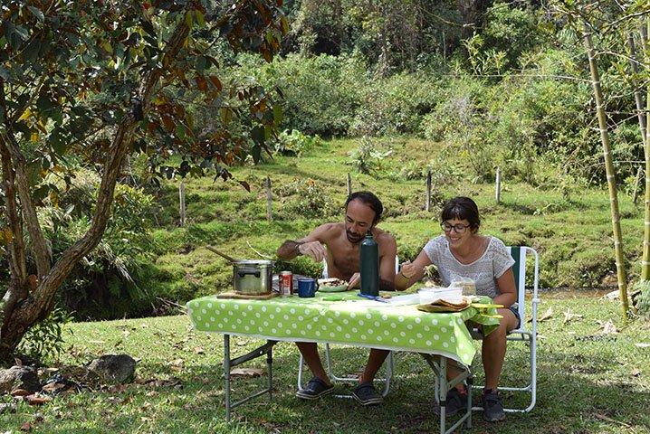 Lidia y Javi de Van Travellers comiendo en el campo en su vuelta al mundo en furgoneta