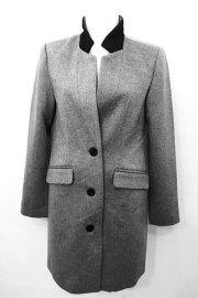 Abrigo de paño en color gris, con botones y cuello en negro.