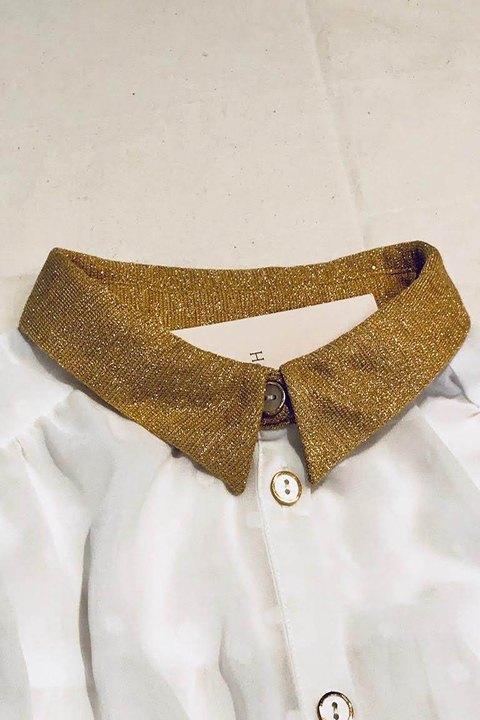 Detalle del cuello dorado y los botones.