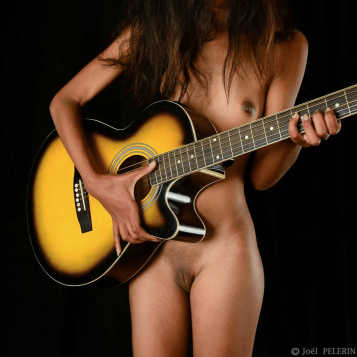 Jouant nue à la guitare