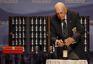 Richard Cole, one of four surviving members of the 1942 raid on Tokyo led by Lt. Col. Jimmy Doolittle opens an 1896 bottle of cognac the raiders had been saving for their final toast, Saturday, Nov. 9, 2013, at the National Museum of the Air Force in Dayton, Ohio. (AP Photo/Al Behrman)