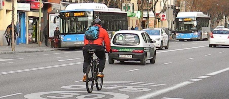 Ciclista urbano en Madrid circulando con corrección, tomando el centro del carril.