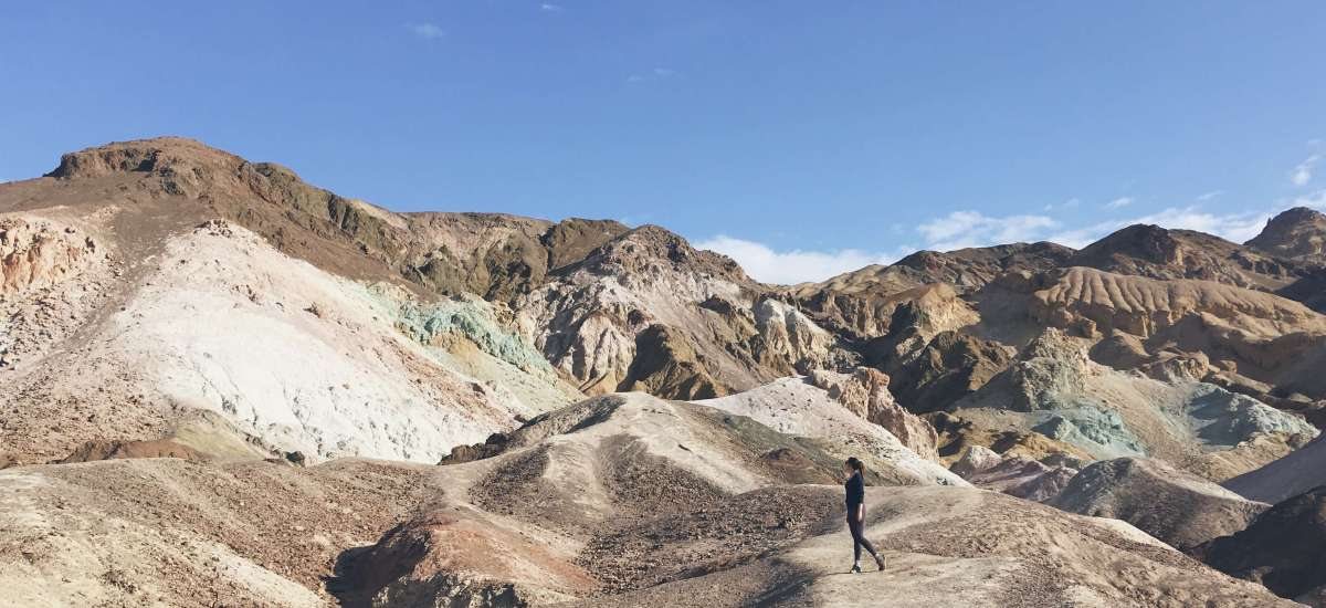 Hanna posing on mountain colored by minerals and metals, Death Valley National Park, California