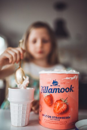 How to Throw a Fun and Easy Summer Soiree by popular Nashville blog Modern Day Moguls: image of young girl putting a scoop of strawberry Tillamook ice cream into a white ice cream cone serving dish.