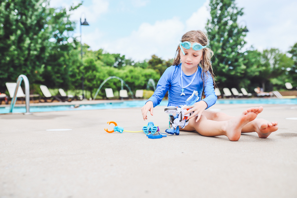 Rescue Heroes Toys: Play Time That Could Teach All Of Us Something by popular life and style blog, Modern Day Moguls:  image of a little girl sitting by a swimming pool and playing with Rescue Heroes toys.