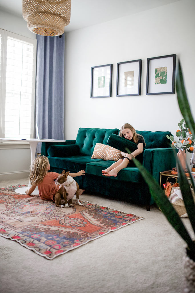What to Look for When Buying Furniture Online by popular lifestyle blog, Modern Day Moguls: image of two girls and a dog playing in a room with a Joybird green tuft velvet couch, orange oriental rug, and joybird white end table.