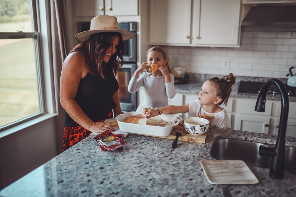 Kid Friendly​ Meal Prep Ideas ​: Back to School Edition by popular Nashville life and style blog, Modern Day Moguls: image of a mom and her two daughters in the kitchen making oven baked sandwiches with Sargento sliced cheese.