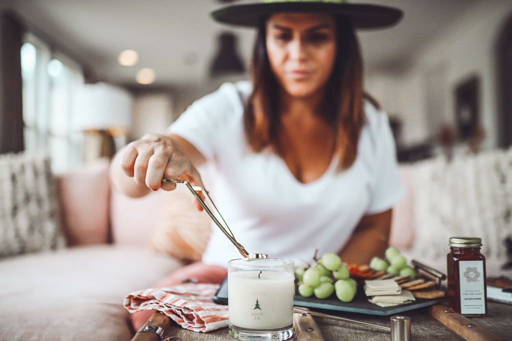 Luxury Trapp Candles Create Hygge This Holiday Season by popular Nashville lifestyle blog, Modern Day Moguls: image of a woman cutting the wick on a Trapp candle.