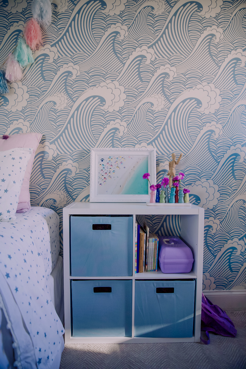 Girls Bedroom Redo: Mermaid, Unicorn, and Rainbows Oh My! by popular Nashville lifestyle blog, Modern Day Moguls: image of a cube organizer, blue storage bins, and ocean waves wallpaper.