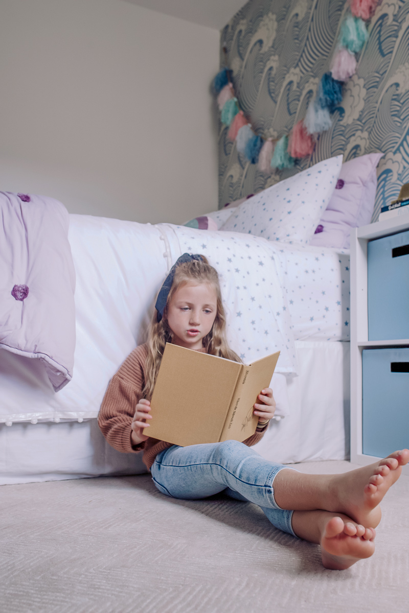 Girls Bedroom Redo: Mermaid, Unicorn, and Rainbows Oh My! by popular Nashville lifestyle blog, Modern Day Moguls: image of a girl leaning up against her bed and reading a book.