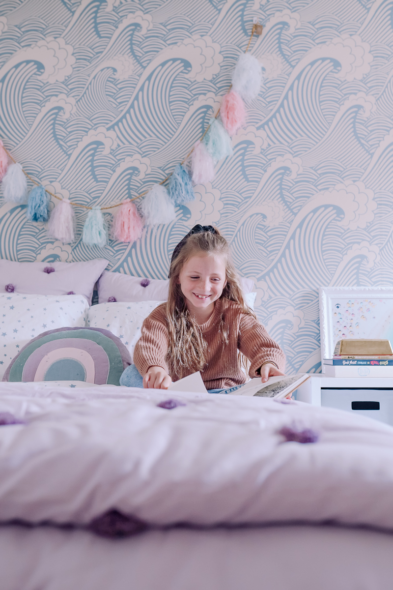 Girls Bedroom Redo: Mermaid, Unicorn, and Rainbows Oh My! by popular Nashville lifestyle blog, Modern Day Moguls: image of a girl reading a book on her bed.