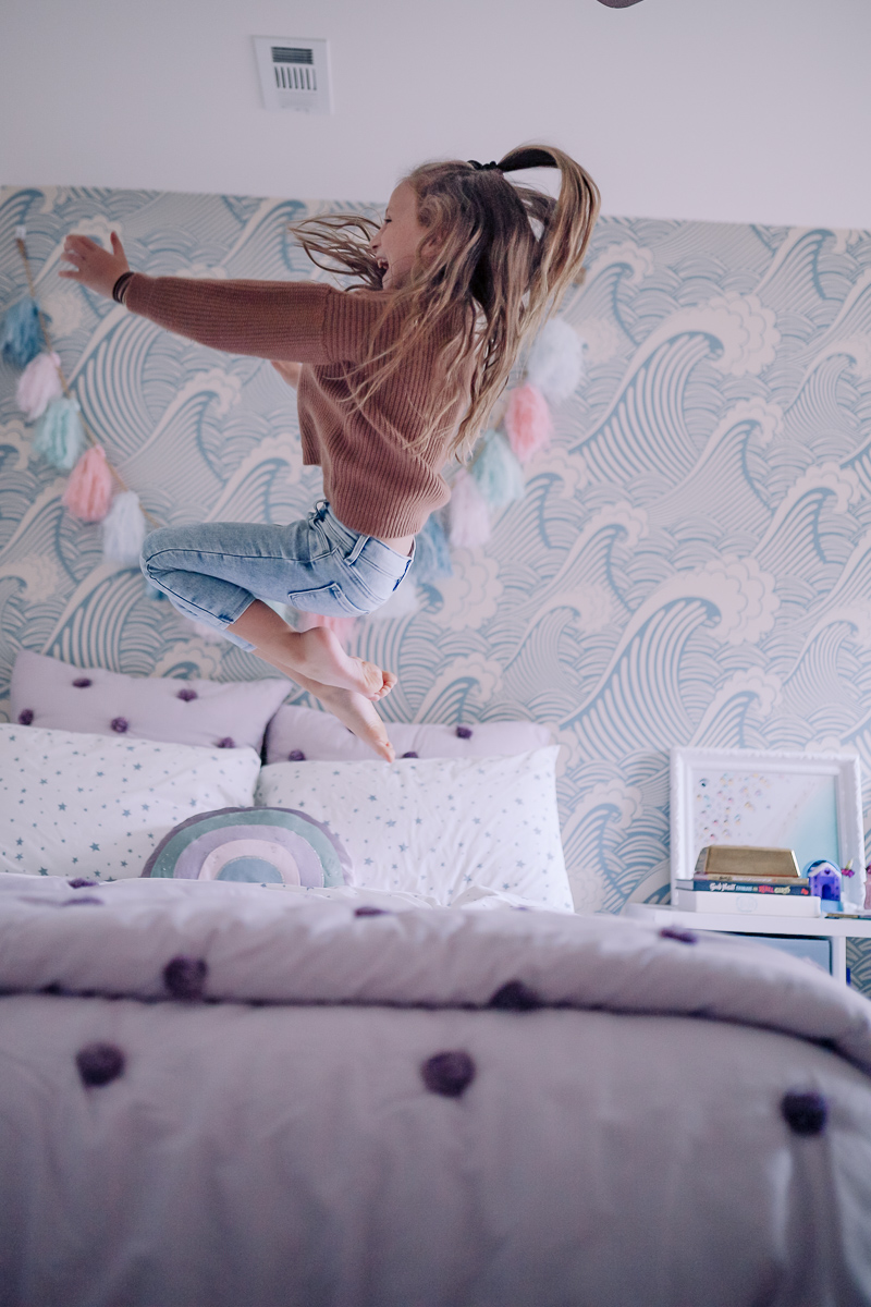 Girls Bedroom Redo: Mermaid, Unicorn, and Rainbows Oh My! by popular Nashville lifestyle blog, Modern Day Moguls: image of a girl jumping on her bed.