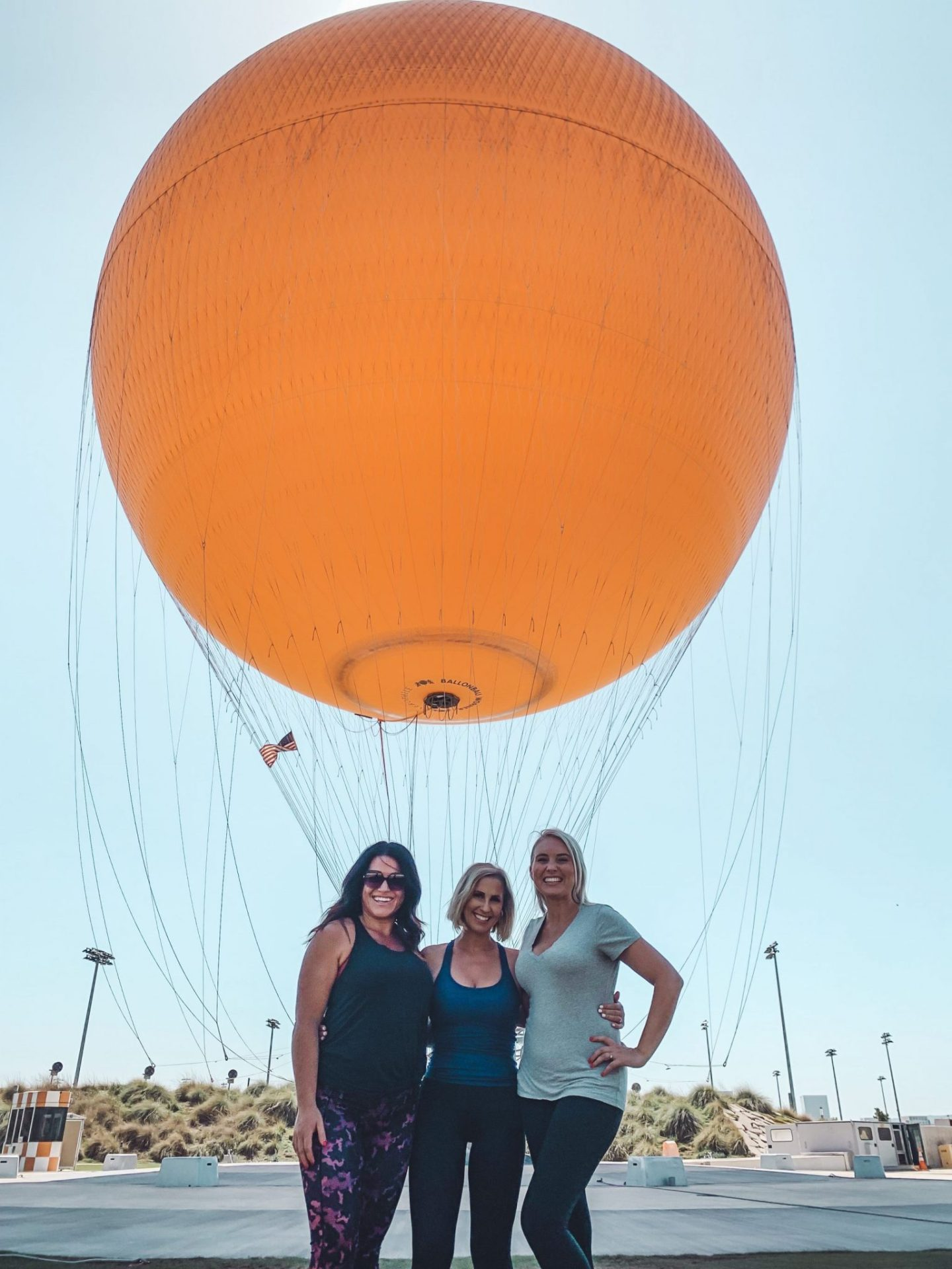 California Vacation Ideas for a Momcation in Orange County by popular Nashville travel blog, Modern Day Moguls: image of three women standing in front of a hot air balloon.