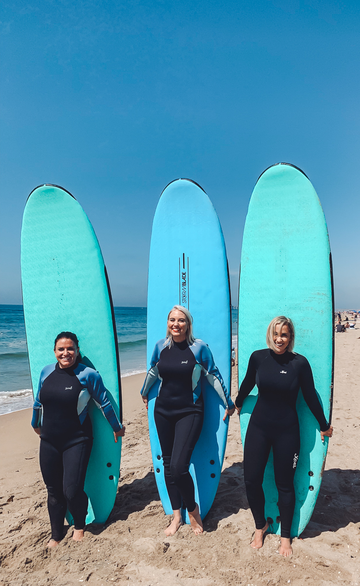 California Vacation Ideas for a Momcation in Orange County by popular Nashville travel blog, Modern Day Moguls: image of three women standing in front of some surf boards.