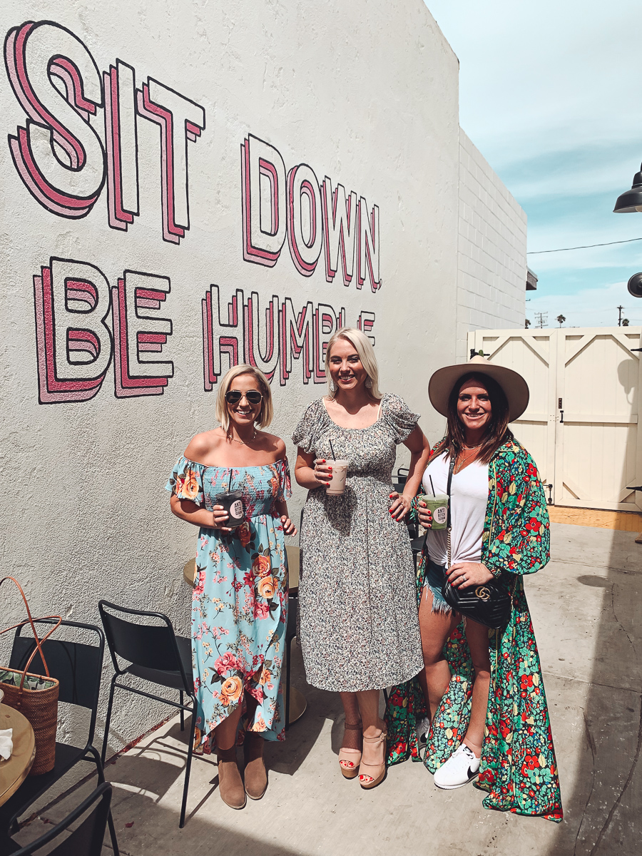 California Vacation Ideas for a Momcation in Orange County by popular Nashville travel blog, Modern Day Moguls: image of three woman standing together outside and holding juices in their hands.