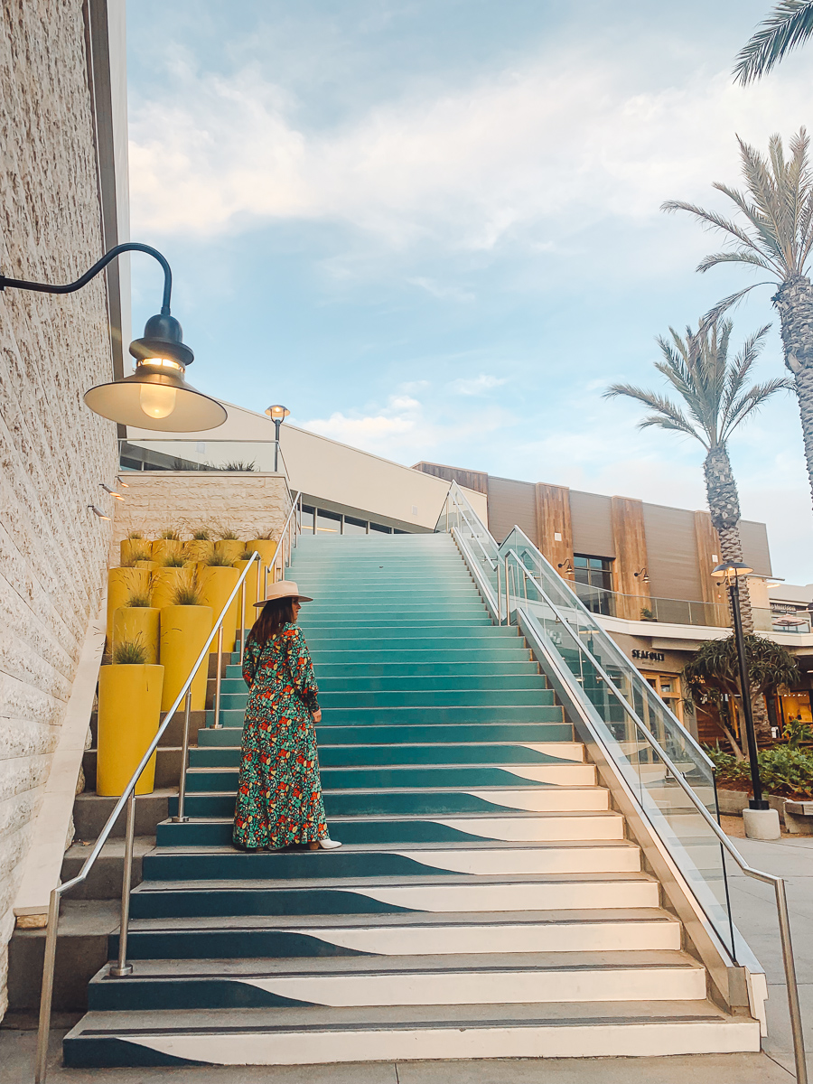 California Vacation Ideas for a Momcation in Orange County by popular Nashville travel blog, Modern Day Moguls: image of a woman standing on some blue steps.