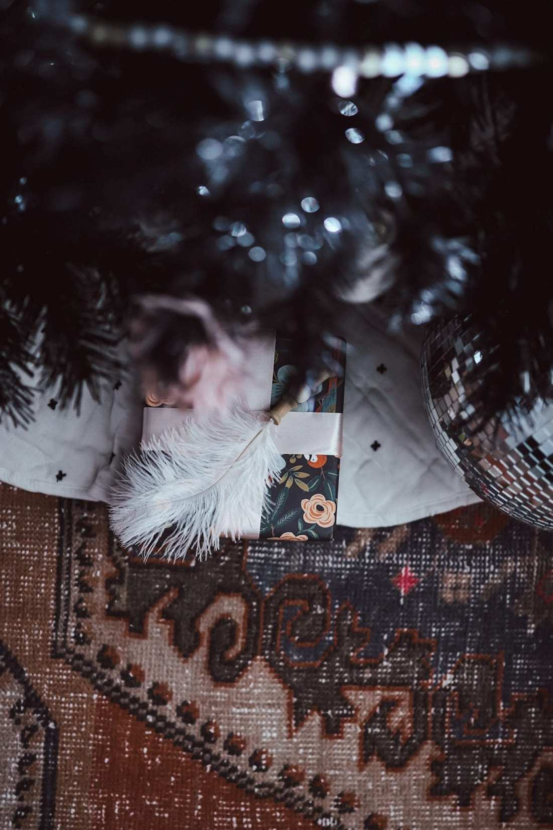 5 Ways to Decorate with Feathers for Boho Christmas Decor by popular Nashville lifestyle blog, Modern Day Moguls: image of a Christmas tree and present decorated with Oriental Trading Feathers, Wooden Beads, and Matte Ornaments.