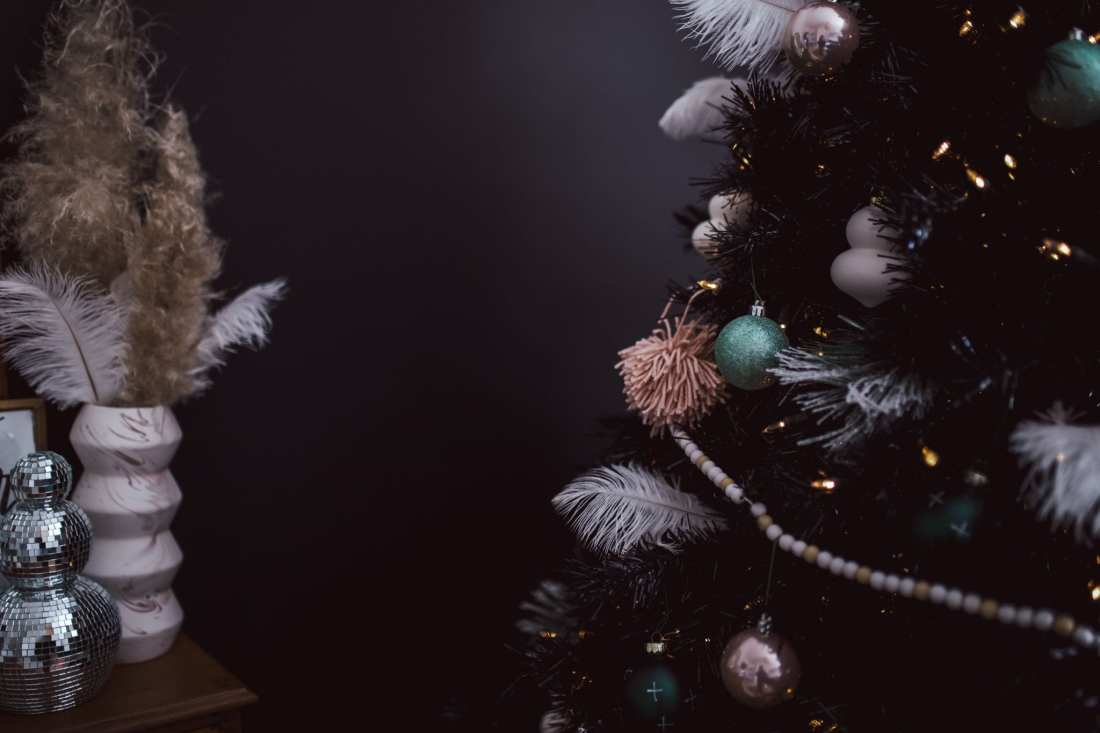 5 Ways to Decorate with Feathers for Boho Christmas Decor by popular Nashville lifestyle blog, Modern Day Moguls: image of a Christmas tree decorated with Oriental Trading Feathers, Wooden Beads, and Matte Ornaments.