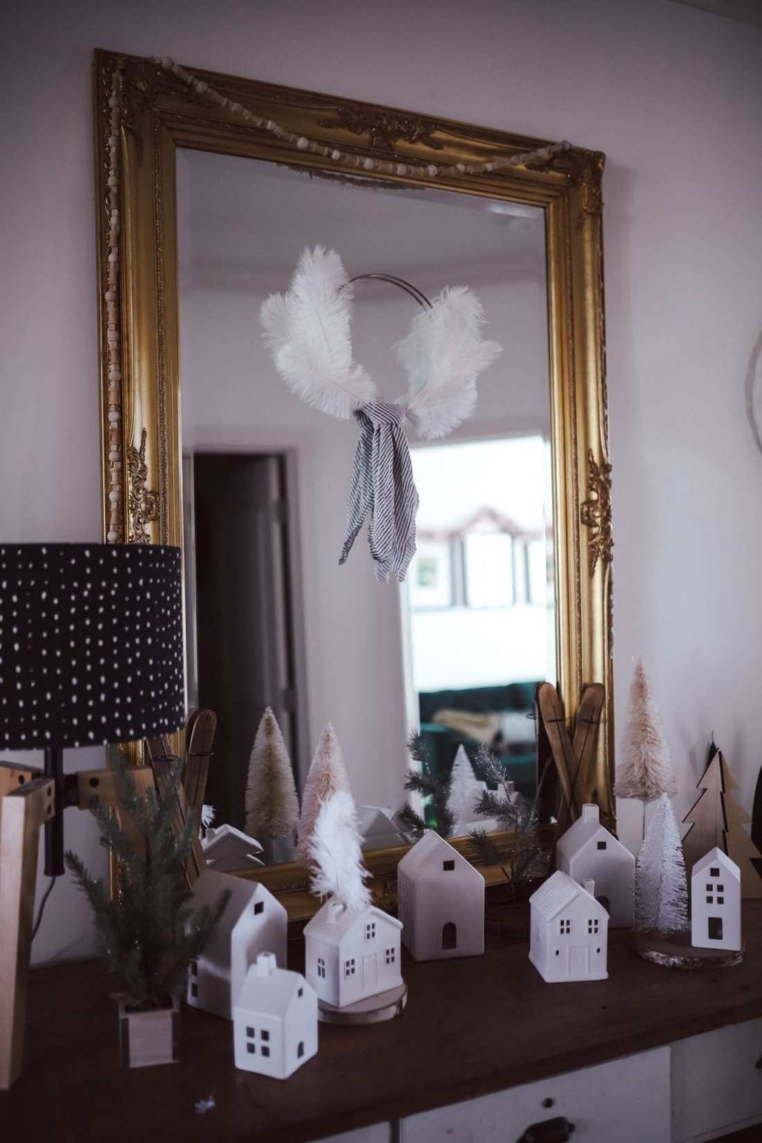 5 Ways to Decorate with Feathers for Boho Christmas Decor by popular Nashville lifestyle blog, Modern Day Moguls: image of a dresser and mirror decorated with Oriental Trading Feathers and Wooden Beads.