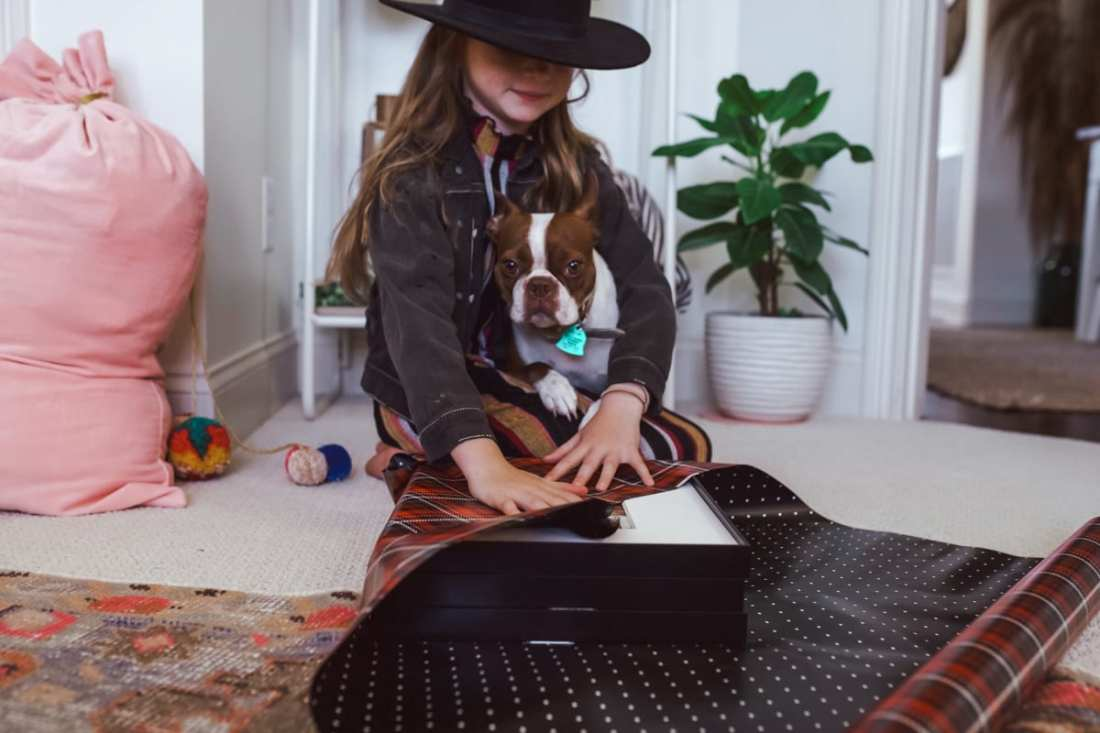 Picture Frames: Gift Ideas From a Child by popular Nashville life and style blog, Modern Day Moguls: image of a girl holding a dog in her lap and wrapping some pictures frames.