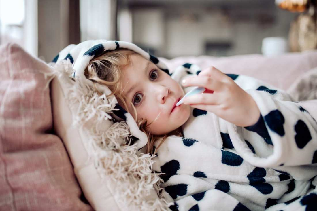 Acetaminophen for Flu by popular Nashville lifestyle blog, Modern Day Moguls: image of a little girl laying on a couch with a thermometer in her mouth.
