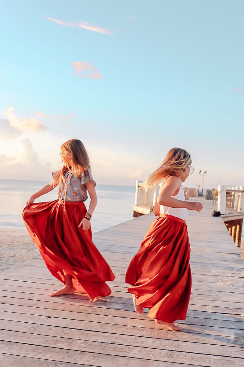 Visiting Turks and Caicos with Kids by popular Nashville travel blog, Modern Day Moguls: image of two little girls dancing on a pier in Turks and Caicos.