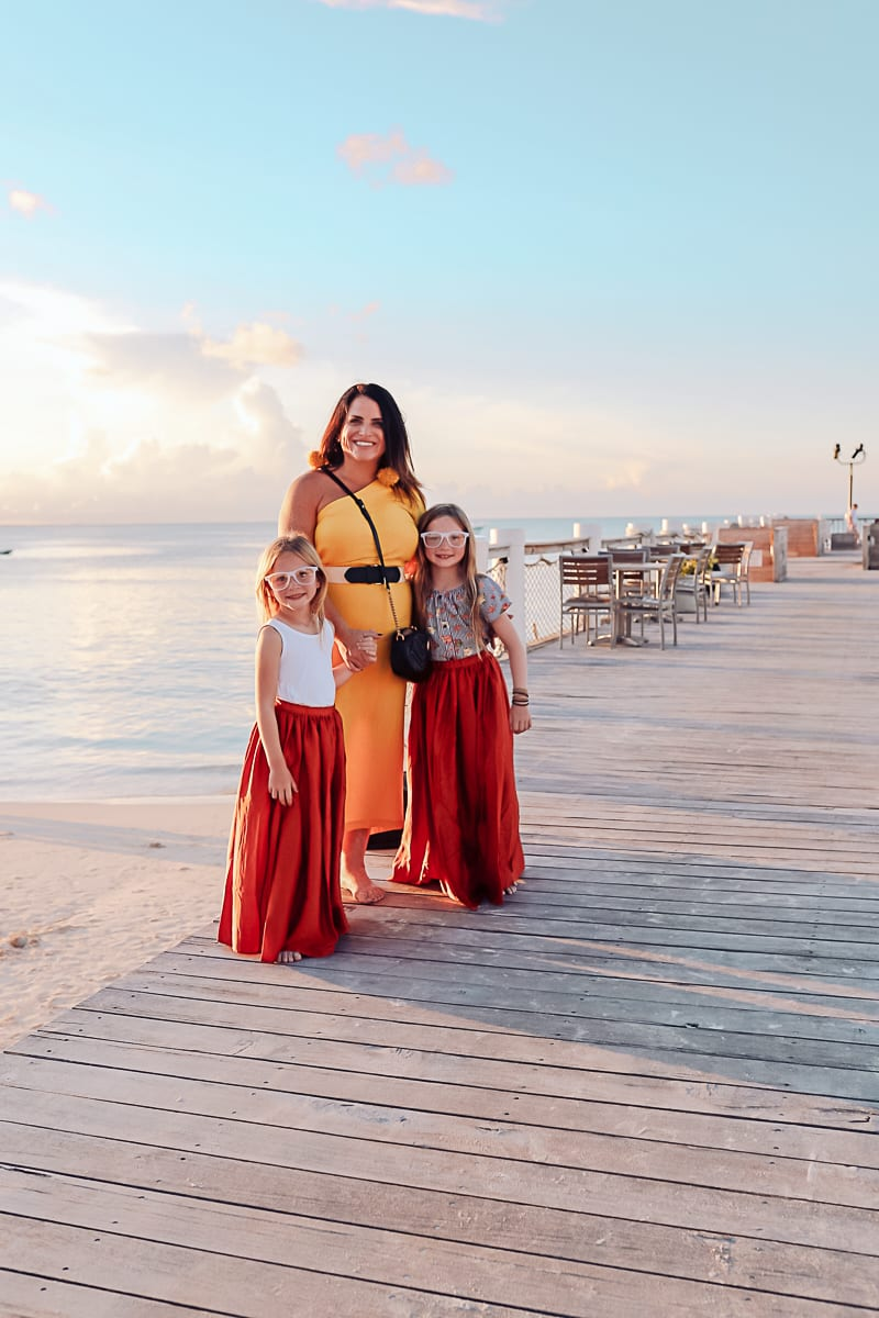 Visiting Turks and Caicos with Kids by popular Nashville travel blog, Modern Day Moguls: image of a mom standing with her two girls on the beach in Turks and Caicos.