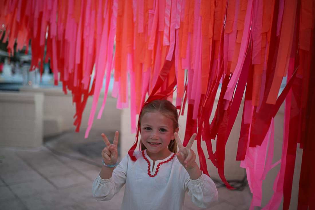 Visiting Turks and Caicos with Kids by popular Nashville travel blog, Modern Day Moguls: image of a little girls standing in front of pink and red streamers.