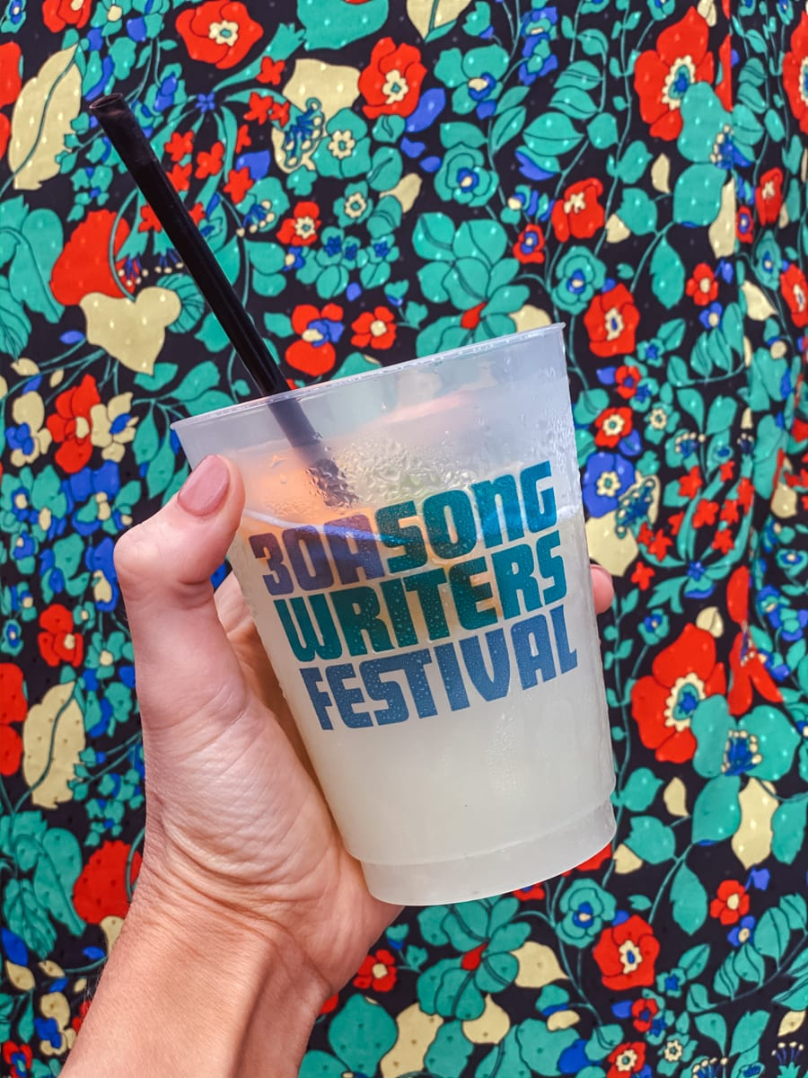 30a Songwriters Festival by popular Nashville life and style blog, Modern Day Moguls: image of a woman holding a 30a Songwriters Festival cup.