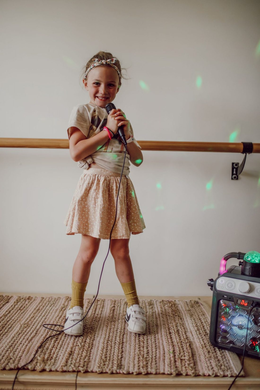 Homeschooling Journey by popular Nashville lifestyle blog, Modern Day Moguls: image of a little girl standing on a stage in singing in a karaoke machine.