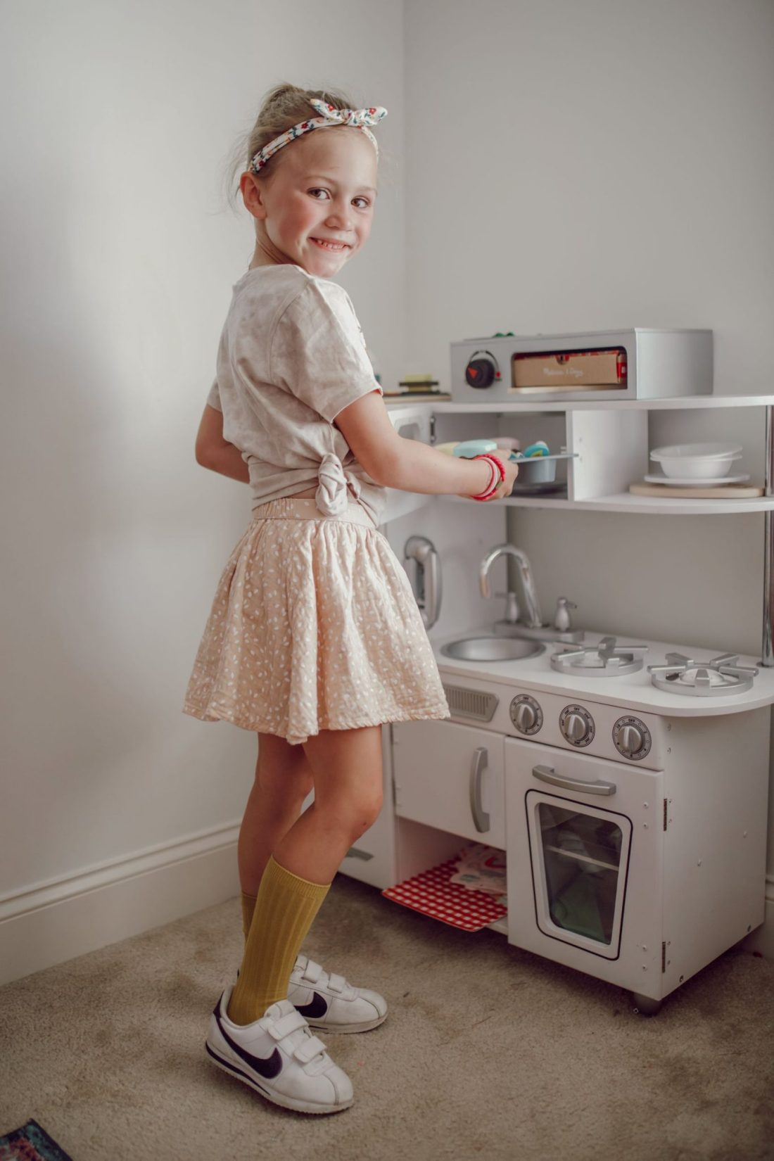Homeschooling Journey by popular Nashville lifestyle blog, Modern Day Moguls: image of a little girl playing with a play kitchen set.